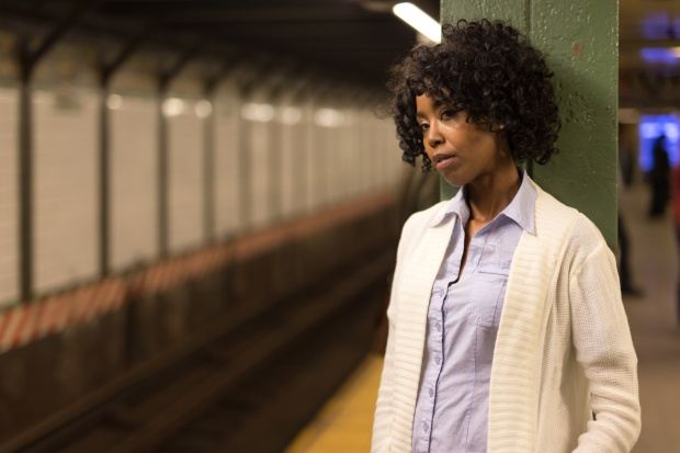 Young African American black woman in city at night waiting for subway train